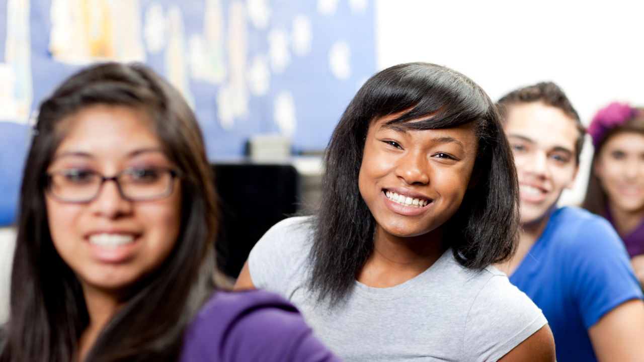 Student smiling with others in computer lab