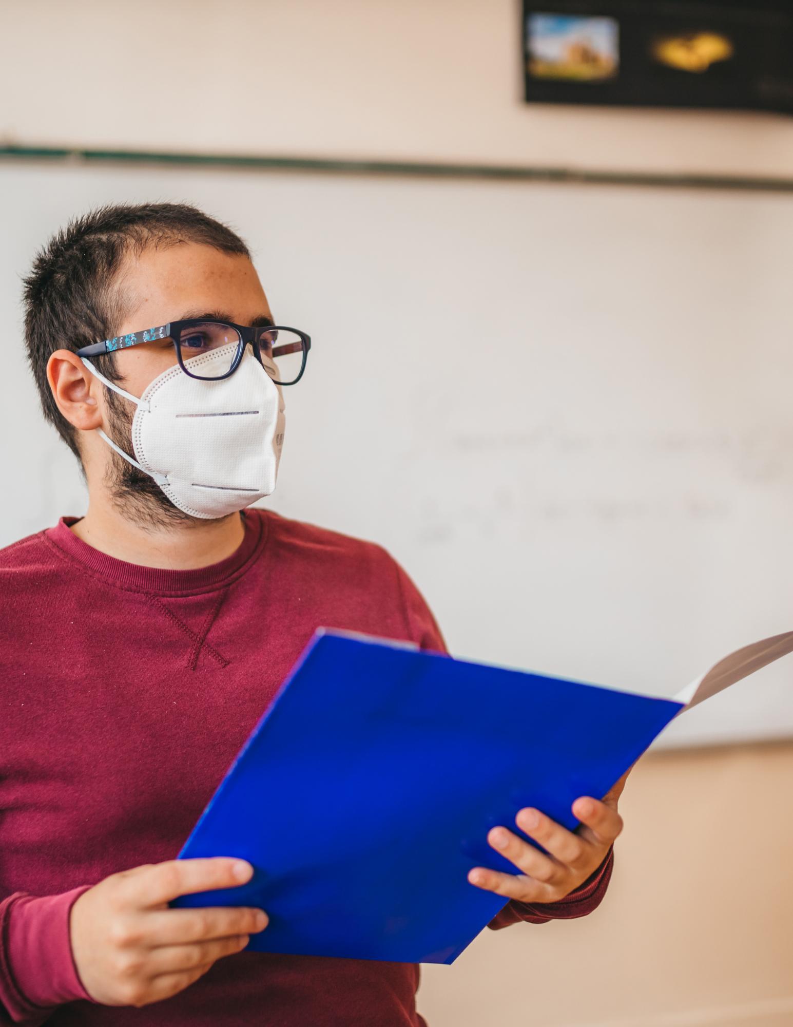 Teacher wearing face mask at head of classroom